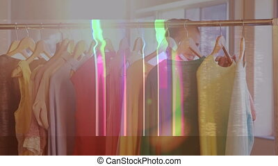 Digital animation of sales text in static effect against woman selecting dresses in a boutique. global retail business concept