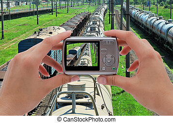 photographing train - digital camera in hand of ...