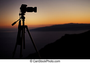 Professional digital camera over the sunset background