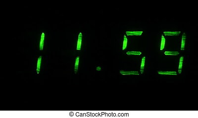 Digital clock shows the time of 11 hours 59 minutes to 12 hours 00 minutes