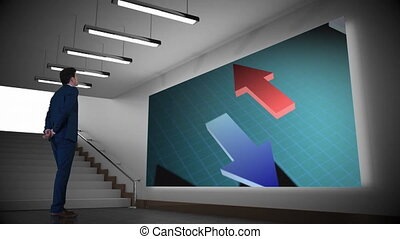Digital composite of a businessman watching animated arrow icons