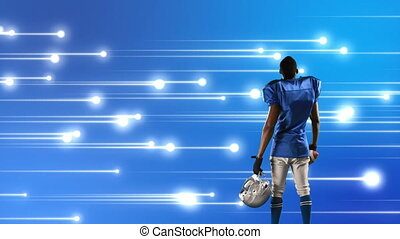 Digital composite of an African-American football player with glowing lights in the blue background