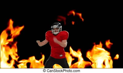 Digital composite of an American football player with a football and background of burning fire