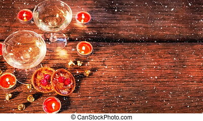 Candles and two glasses on wood combined with falling snow