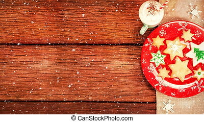 Christmas cookies and hot drink on wood combined with falling snow