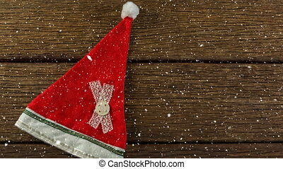 Falling snow with Christmas Santa hat on wood