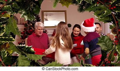 Family Christmas gift ceremony with holly border