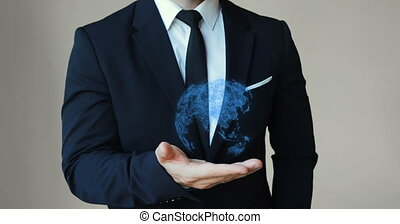 Digital composite of Hand presenting a global community graphic. businessman holding a hologram of planet earth in his hand