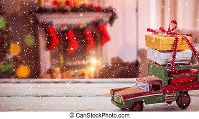 Model car with presents on its roof and blurred background of a living room decorated for christmas