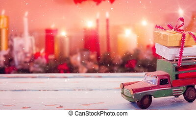 Model car with presents on its roof and blurred background of candles combined with falling snow