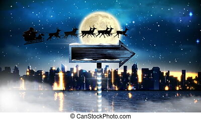 Digital composite of Santa in sleigh with reindeer flying and arrow sign over night city with moon