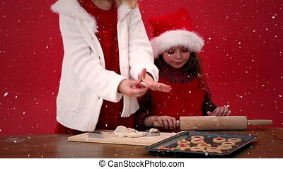 Video composition with falling snow over desk with kids preparing cookies