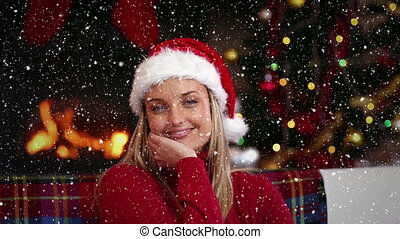 Video composition with falling snow over happy girl in santas suit sitting at couch in room with fir