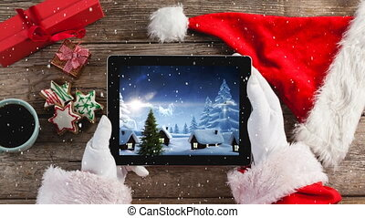 Video composition with snow over of top view of santa holding tablet