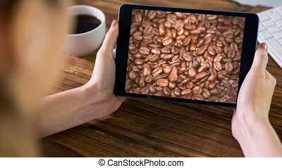 Woman using tablet with coffee beans