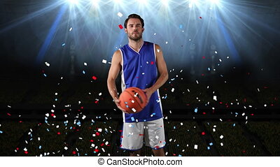 Digital composite video of Confetti falling over male basketball player holding a basketball against flood lights on black background. Sports fitness concept digital composite