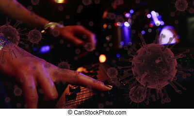 Animation of macro Covid-19 cells floating over a DJ using a sound mixer. Coronavirus Covid-19 pandemic concept digital composite