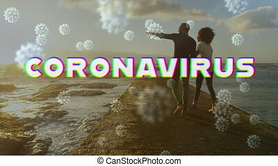 Digital composite video of Covid-19 cells moving against couple watching sea shore in background
