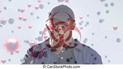 Animation of a hazard sign with macro Covid-19 cells floating over mixed race man using walkie talkie. Coronavirus Covid-19 pandemic concept digital composition