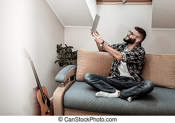 Cheerful delighted man holding a laptop in his hands