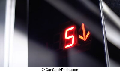 Digital display in the elevator which descends from the 7th to the 1st floor with an arrow down