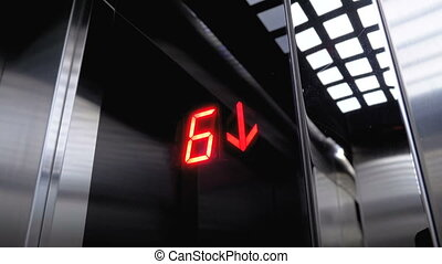 Digital display in the elevator which descends from the 7th to the 2st floor with an arrow down