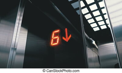 Digital display in the elevator which descends from the floor with an arrow down