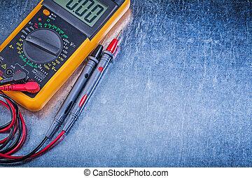 Digital electric tester on metallic background.