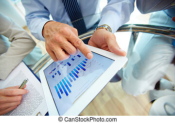 Close-up of a modern business team using tablet computer to work with financial data