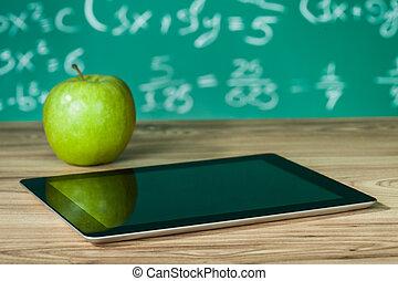 Digital tablet and apple on the desk