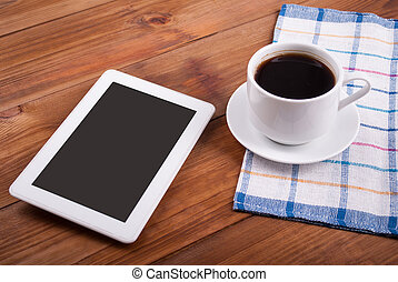 Digital tablet and coffee cup on a wooden table.
