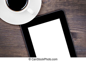 Digital tablet and coffee cup on table