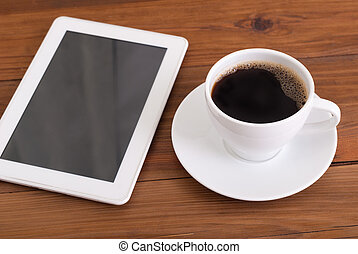 Digital tablet and cup of coffee on wooden desk.