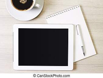 digital tablet and cup of coffee on wooden table