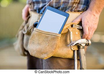 Digital Tablet And Hammer In Carpenter's Tool Belt - Closeup...