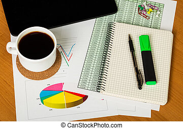Digital tablet, coffee cup and notebook with pen on desktop.