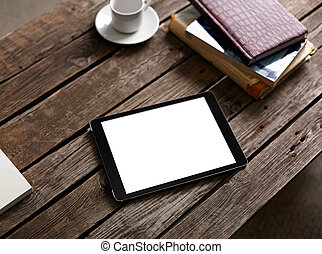 Digital tablet on wooden table with cup of coffee