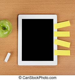 Digital tablet over a school desk with post-it
