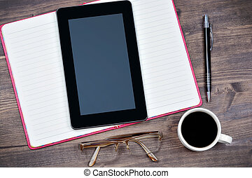 Digital tablet pc with notebook, coffee and pen on desk