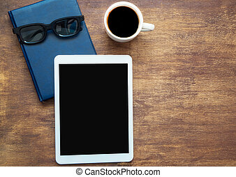 Digital tablet with black blank space on the screen and cup of coffee, Copy space. Closed blue notebook with black glasses on it, top view