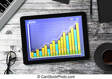Digital tablet with business graph on a wooden table