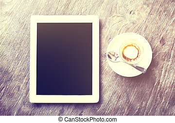 Digital tablet with cup of coffee on a wooden table