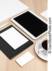 Digital tablet with notepad, supplies and coffee cup on desktop.