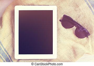 Digital tablet with sunglasses on a beach towel