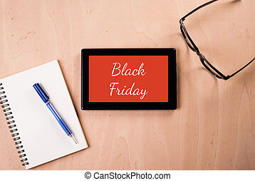 """Digital tablet with the inscription: """"Black Friday"""", the subject lay on a wooden table: glasses, Notepad,"""