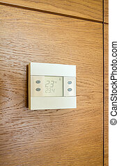 Digital thermostat panel on wooden wall - Digital thermostat...