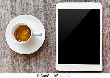 digital white tablet and coffee cup on wooden table