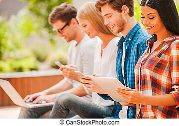 Digital world. Group of happy young people holding different digital devices and smiling while sitting in a row outdoors