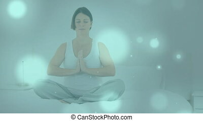 Digitally generated video of glowing spots moving against pregnant woman performing yoga in backgrou