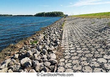 dike and lake - stone dike along a lake in the netherlands